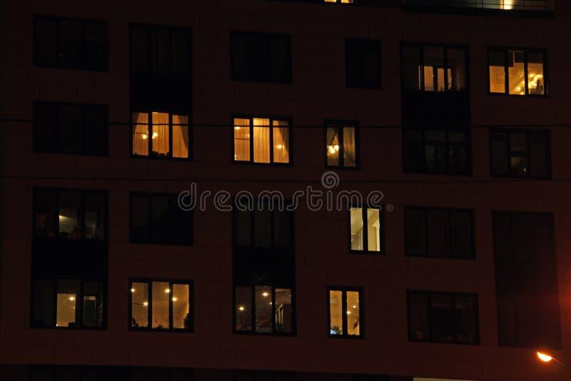 Finestre di notte dell'edificio residenziale di palazzo multipiano nell'area di sonno della città immagine stock libera da diritti