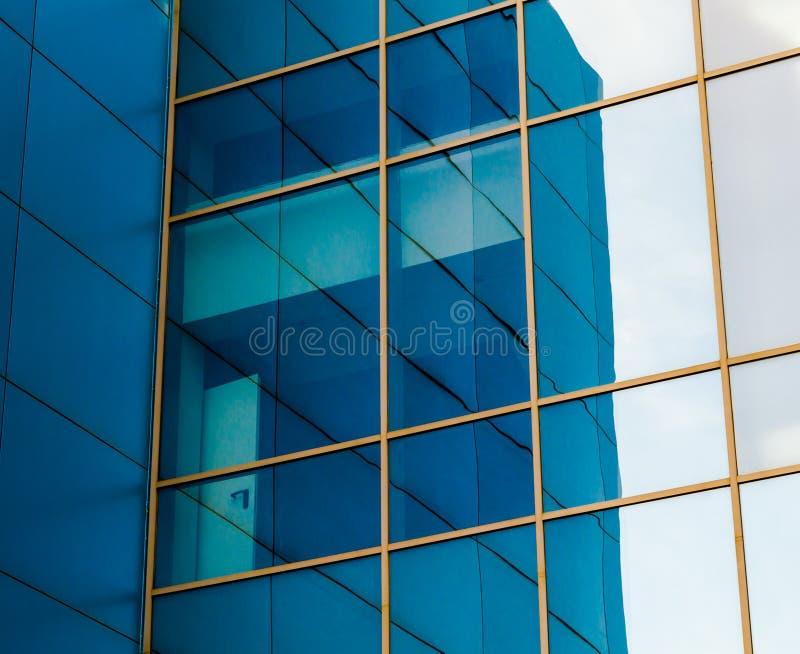 Finestre rispecchiate della facciata di un edificio per uffici con la p blu fotografia stock