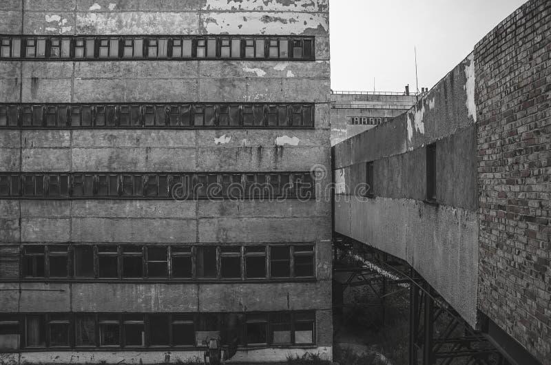 Finestre rotte in un vecchio fabbricato industriale abbandonato immagine stock