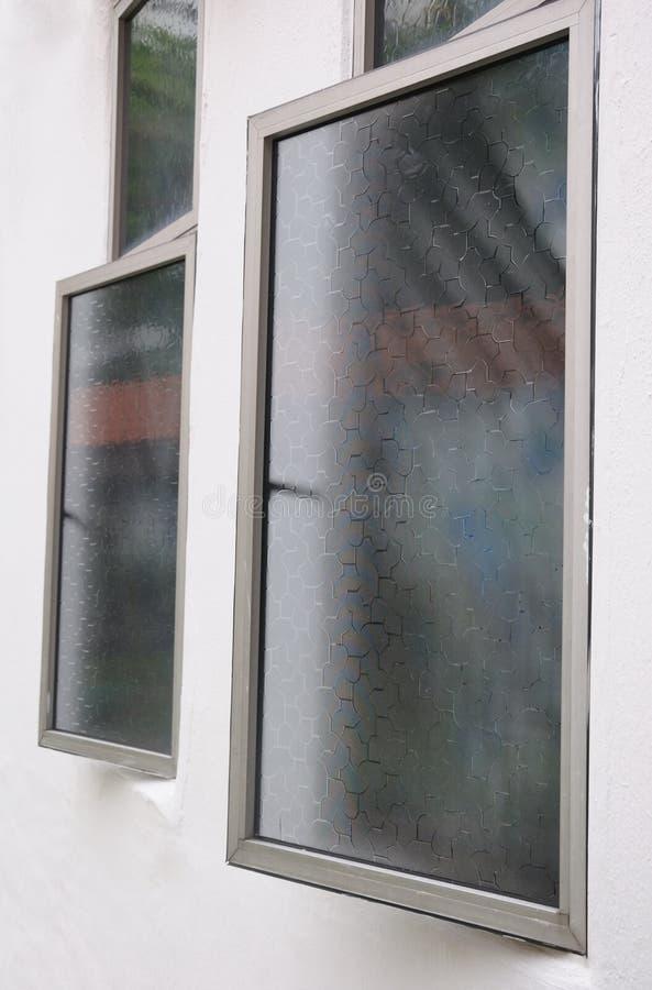 Finestre socchiuse della stoffa per tendine con i film della finestra immagini stock