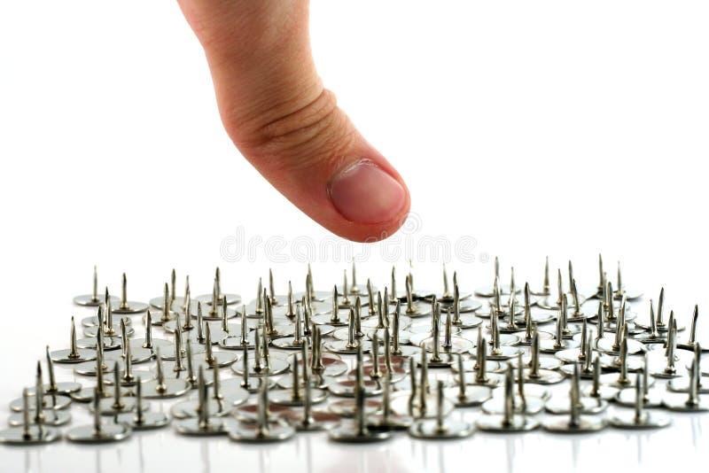 Finger above thumb tacks - drawing pins royalty free stock photography