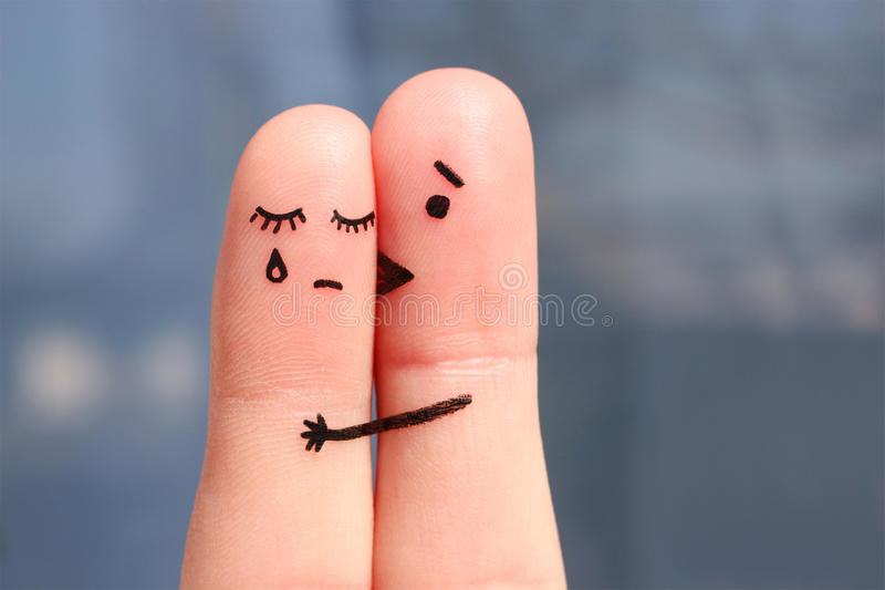 Finger art of displeased couple. Woman cries, man reassures her. royalty free stock images