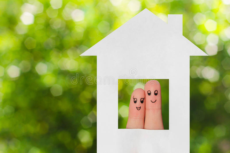Finger art of a family. Family looking out of the window of the house out of paper. stock photo