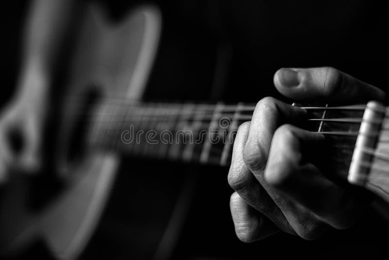Finger auf Gitarrenschnüren in Schwarzweiss lizenzfreie stockfotografie