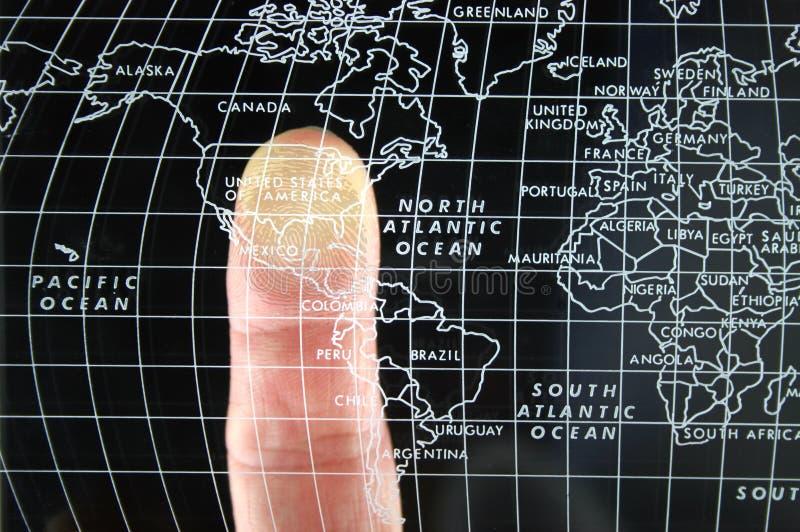 Finger auf Weltkarte stockfotos