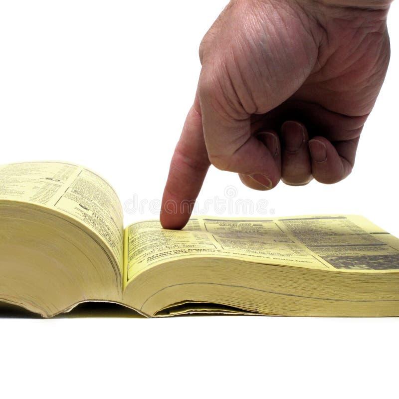 Finger av handen som pekar på gula sidornaboken royaltyfri bild