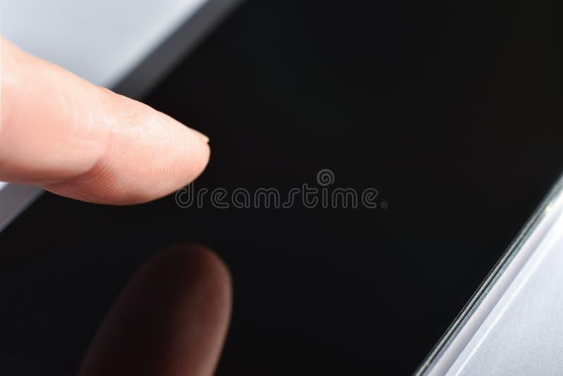 Finger berührt den Smartphoneschirm mit integriertem Fingerabdruckscanner, weißer Hintergrund stockfotografie