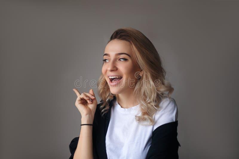 Finger bonito joven de la tenencia de la muchacha para arriba que tiene idea y presentación fotografía de archivo