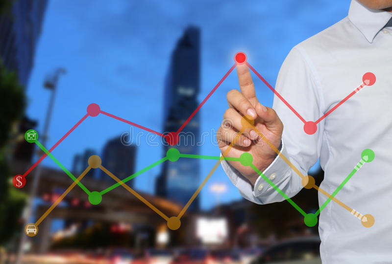 Finger of businessman touch to the peak of business graph on Sky. Scraper background,concept to success and profitability stock photography