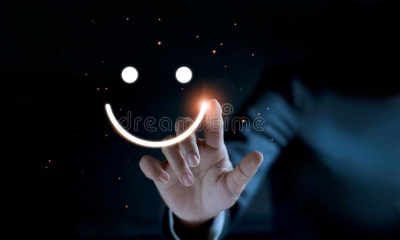 Finger of businessman touching and drawing emoticon face smiling. On dark background, service mind, service rating. Satisfaction and customer service concept stock photos