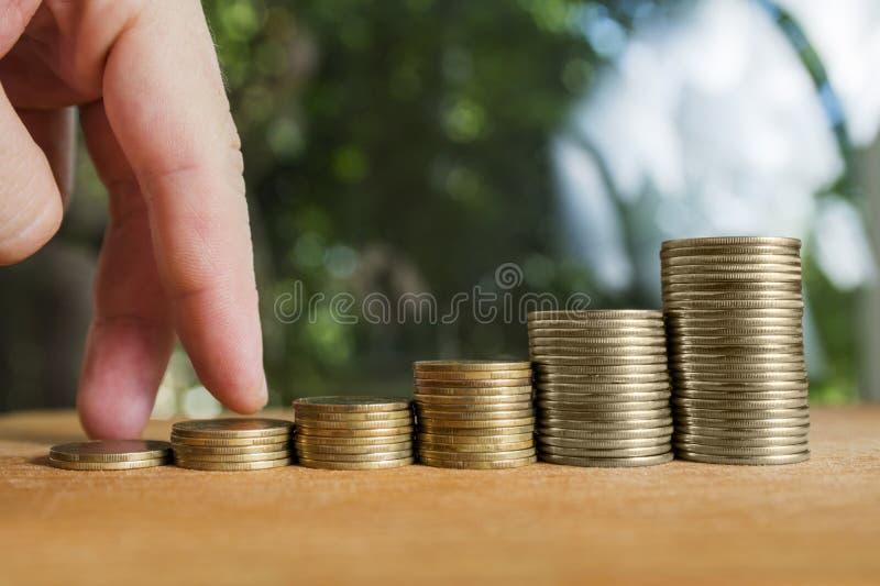 Finger de la mano del hombre que camina en las escaleras de las monedas Pasos del concepto de la realización o de escaleras del é imágenes de archivo libres de regalías