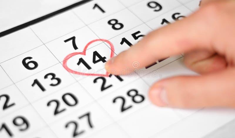 Finger de la mano que señala al 14 de febrero Hoja del calendario con la fecha del 14 de febrero marcada por forma roja del coraz imagen de archivo
