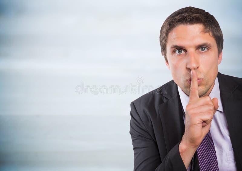 Finger del hombre de negocios sobre boca contra el panel de madera gris foto de archivo libre de regalías