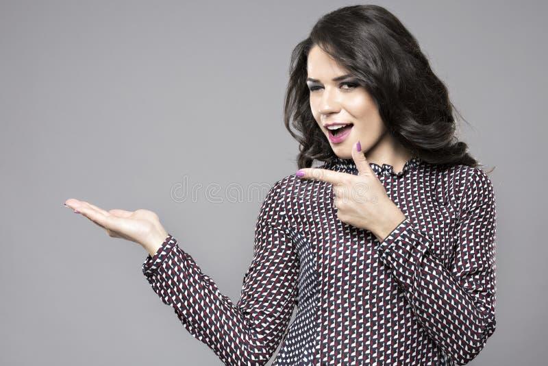 Finger del punto de la sonrisa de la empresaria para vaciar el espacio de la copia, negocio w foto de archivo