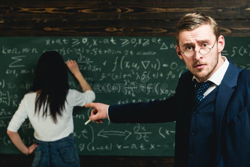 Finger del punto del profesor de escuela en el estudiante que hace sumas Profesor de escuela con los vidrios en cara elegante imagenes de archivo