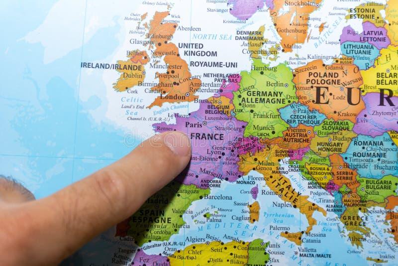 Finger, der auf eine bunte Landkarte von Paris, Frankreich in Europa zeigt stockfotografie