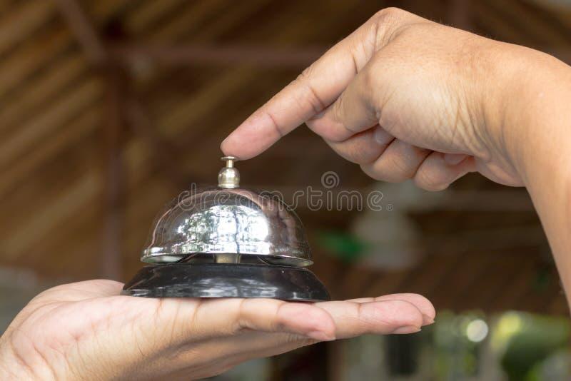 Finger des Mannes drückt auf die silbernes Metallklingelnglocke lizenzfreie stockbilder