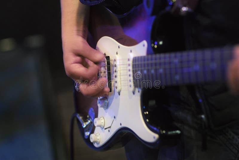 Finger, die auf Bass-Gitarrennahaufnahme spielen lizenzfreies stockbild