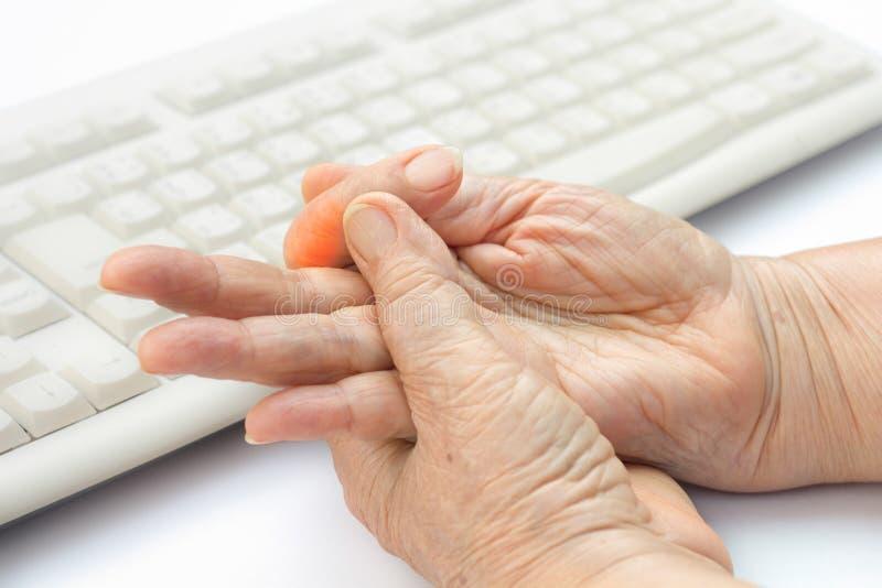 Finger doloroso de la mujer mayor debido al uso del teclado fotografía de archivo