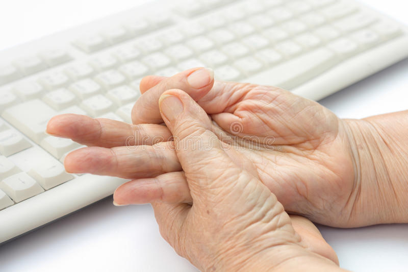 Finger doloroso de la mujer mayor para utilizar el teclado y el ratón imagen de archivo