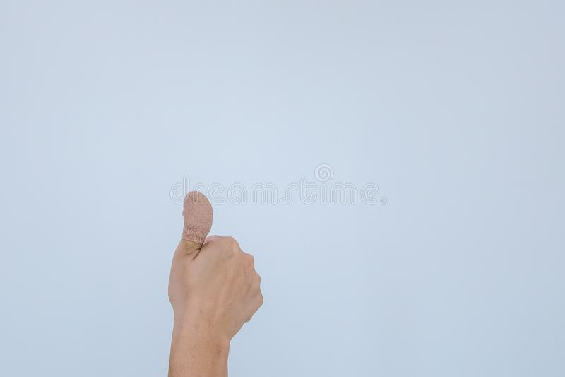 Finger doloroso herido con el vendaje blanco La mano ha sido herida por el accidente y el mostrar pulgar para arriba fotografía de archivo