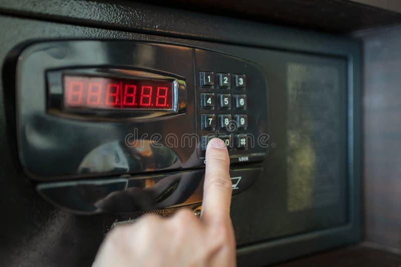 Finger drücken die Zahltasten des elektrischen Safes stockfotografie
