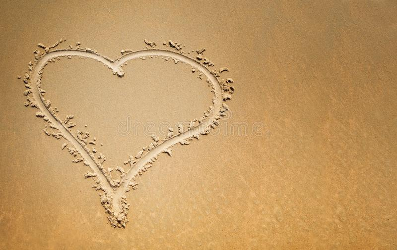 Finger drawn heart on the sand, symbol of love. With copy space stock photos