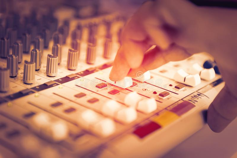 Engineer or music producer controlling sound recording studio mixing desk. Finger of engineer or music producer controlling sound recording studio mixing desk stock photography