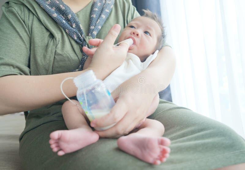 Finger Feeding breast milk to newborn baby boy using small tube royalty free stock photography