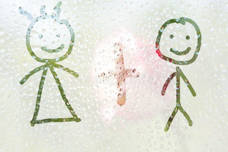 Finger-formad teckning av banden av en pojke och en flicka på ett genomskinligt fördunklat exponeringsglas regndroppar av vårregn arkivfoton