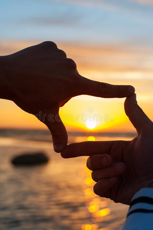 Finger frame- imitation of capturing rays of sunlight on sunset. Composition finger frame- imitation of capturing rays of sunlight on sunset. Multicolored stock image