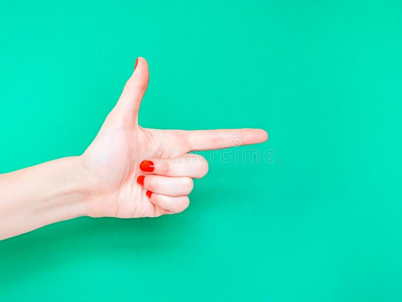 The Finger Gun Hand Sign. Is used as a way to say Yup with your hands. Pointing index finger on isolated turquoise green royalty free stock photo