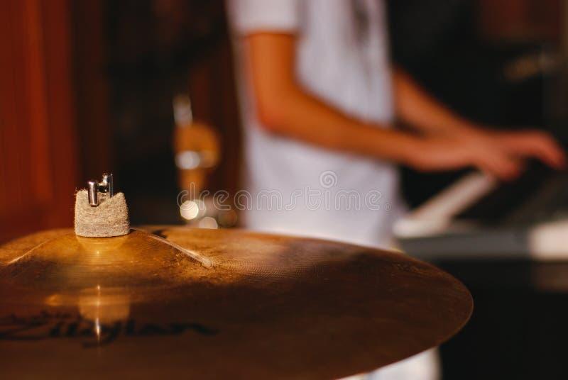 Finger- & handcymbaler i en skymt under repetition med pianisten i bakgrund royaltyfri bild