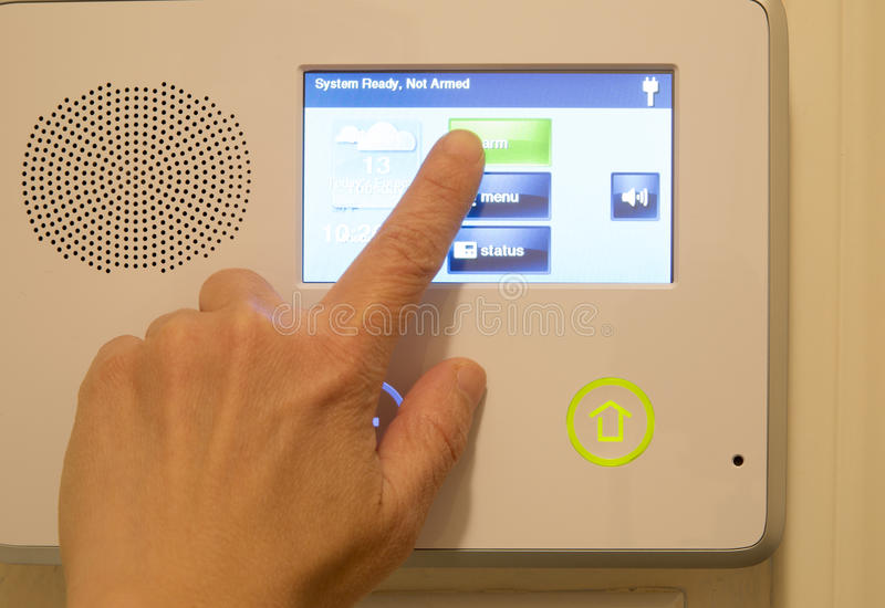 Finger on house security alarm royalty free stock photo