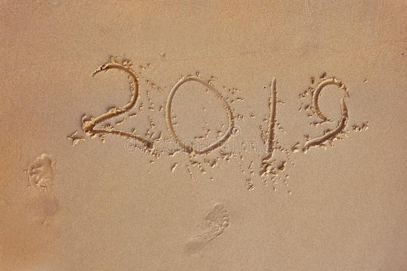 Finger inscription on a sandy beach 2019 and foot prints. The outgoing 2019 year. Concept royalty free stock images