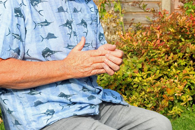 Finger joint pain. Arthritis. Senior in pain. Elderly or senior man holding his fingers or hand because of pains. Arthritis in his joints stock photo