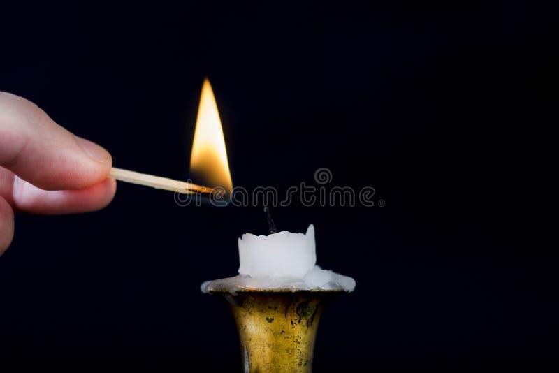 Finger med flamman för Matchstickstartljus på stearinljuset i ljusstake royaltyfria bilder