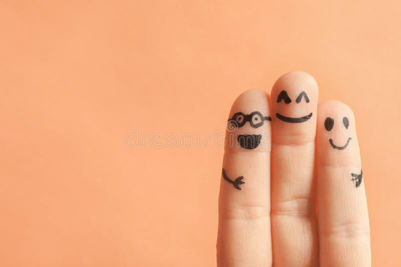 Finger mit Zeichnungen von glücklichen Gesichtern stockbilder