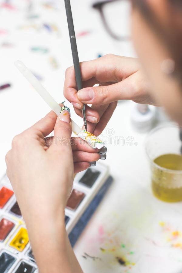 Finger nail treatment, painting flower with brush and lacquer stock photos