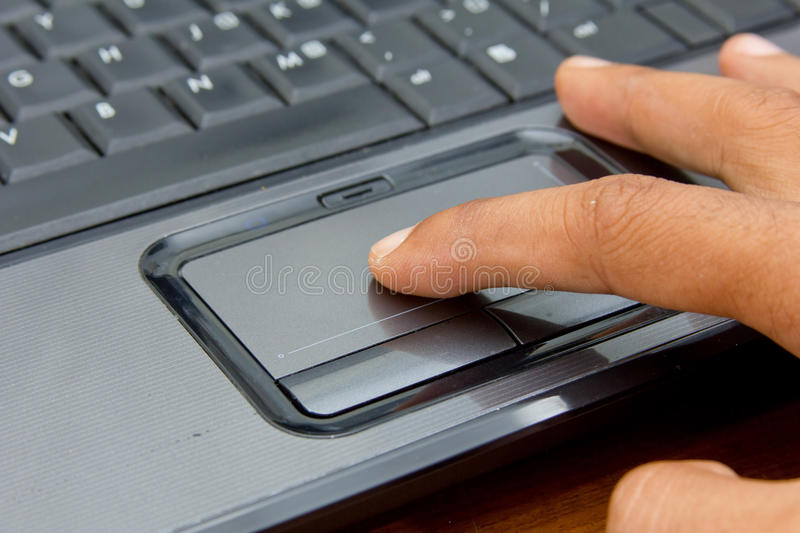 Finger on notebook touchpad. royalty free stock image