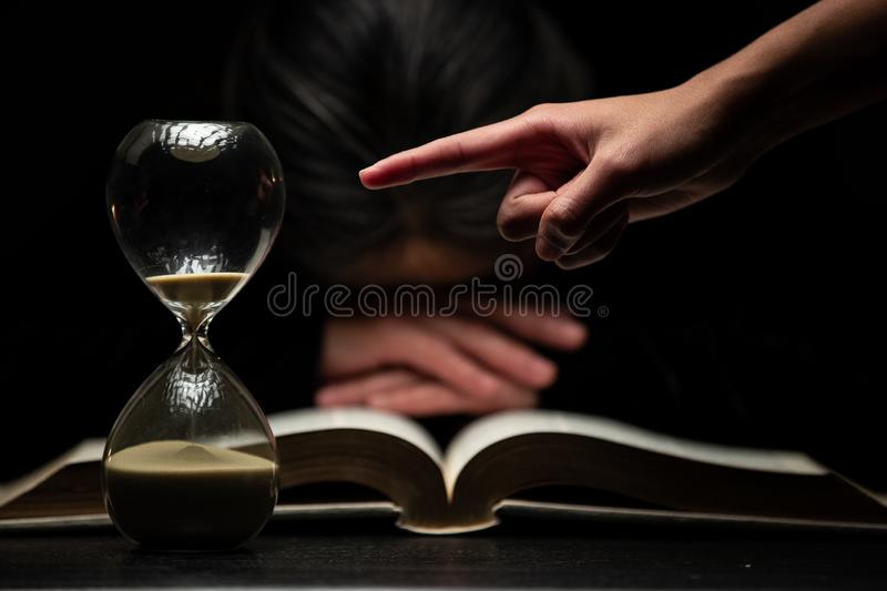 Finger of Person Pointing to Time while Woman Sleeps Over Bible stock photography