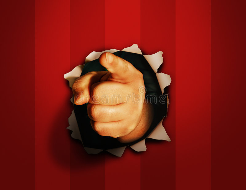 Finger pointed through wall. A view of a hand bursting through a red wall with an index finger pointing directly forward stock images