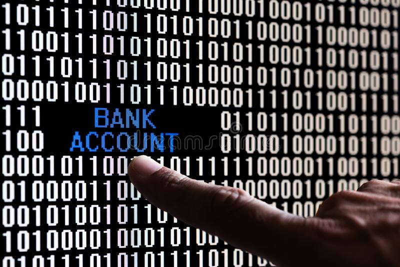 Finger pointing bank account data in binary code. On a computer screen stock photography