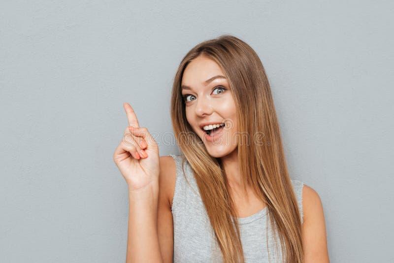 Finger poiting de la mujer feliz joven para arriba en el copyspace fotografía de archivo