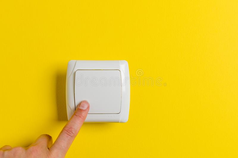 Finger press light switch on a bright yellow background stock photos