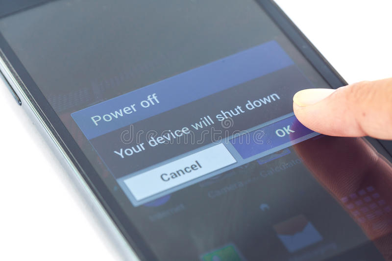 Finger press power off button on smartphone. Close up finger press power off button on smartphone royalty free stock images