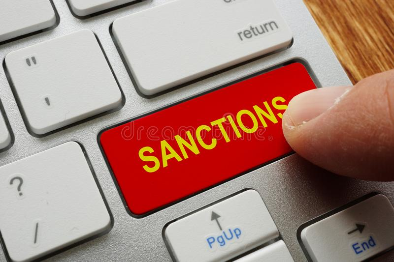 Finger presses the button sanctions. On the keyboard royalty free stock image