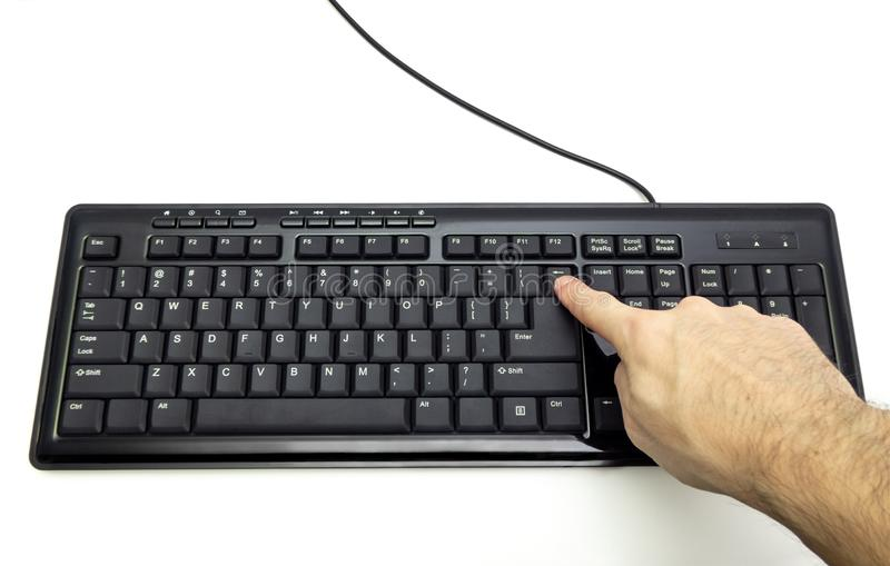 Finger pressing Backspace button on the black keyboard stock photos