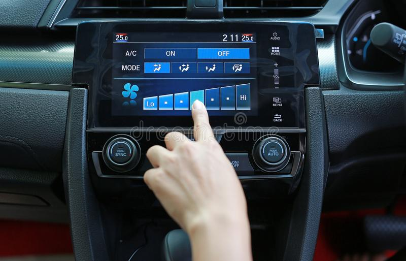 Finger pressing the button adjust speed the air conditioner in the modern car dashboard.  stock photography