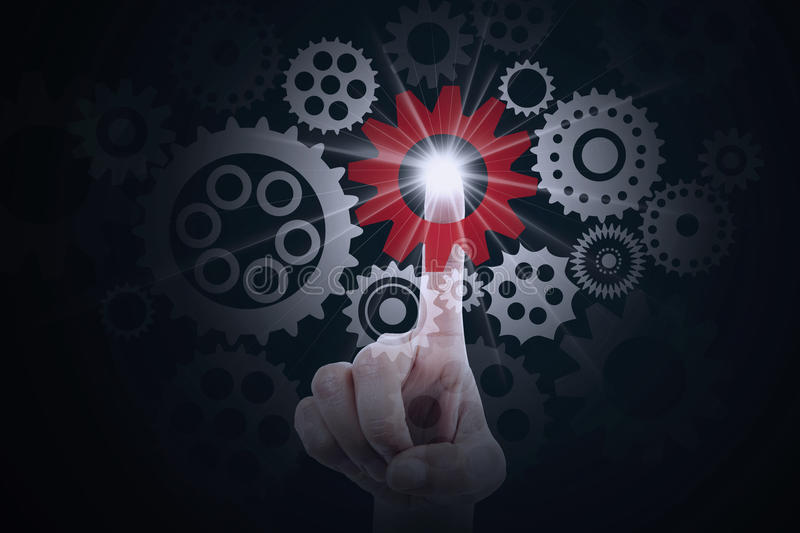 Finger pressing a cog gear. Symbolizing business control stock photo